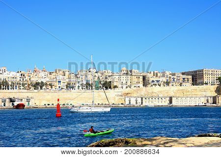 VALLETTA, MALTA - MARCH 31, 2017 - View across the Grand Harbour towards Valletta city seen from Vittoriosa with a yacht and canoe in the foreground Valletta Malta Europe, March 31, 2017.
