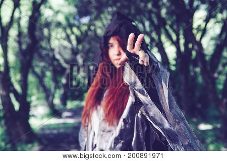Image of witch in black cloak with outstretched hand in dark forest, toned