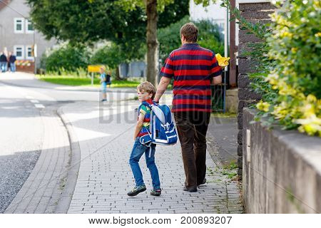 Parent taking child, kid boy to school. Pupil of primary school go study. Father holding hand of little son with backpack outdoors Beginning of lessons. Back to school. First day of fall.
