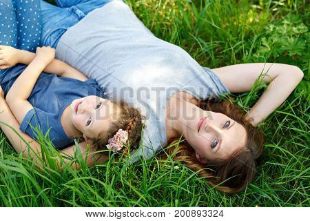 Beautiful young mother and little daughter lying on green grass and resting. Girl and woman hugging in love, playing in the park. Mothers Day concept. Happy smiling family