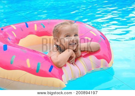 Cute little girl with inflatable donut in swimming pool