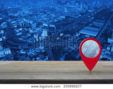 Map pin location button on wooden table over modern office city tower background Map pointer navigation concept