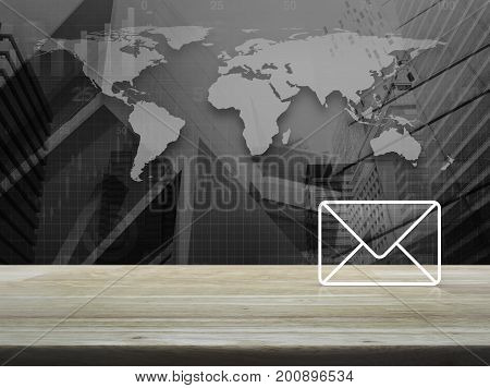 Mail icon on wooden table over world map with financial graph and modern city tower Contact us concept Elements of this image furnished by NASA
