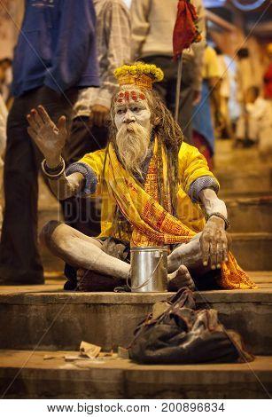 Varanasi India - November 18 2009: A holy man a sadhu sitting on the embankment of Varanasi during a religious ceremony