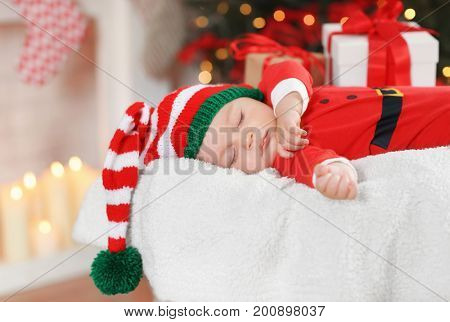 Cute little baby in Santa costume sleeping against blurred Christmas lights background