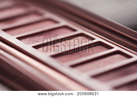 Eye shadow palette in rose gold and nude colors closeup. Makeup cosmetics. Selective focus.