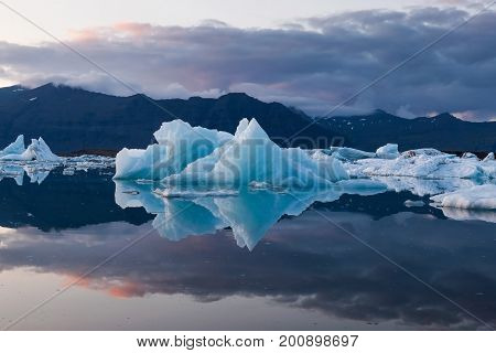 Amazing Sunset With Melting Icebergs Of Emerald Turquoise Blue In Jokulsarlon Glacier Lagoon. Base O