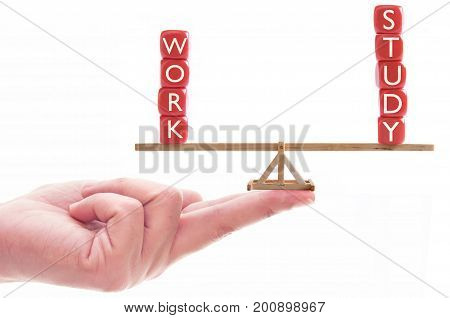 Hand holding seesaw balancing work and study block letters