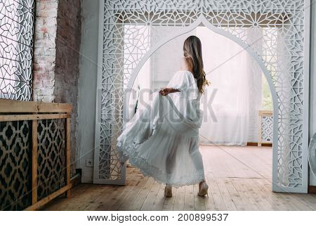 The Beautiful bride is spinning around herself in dance. Cheerful brunette is posing in fluttering dress in a vintage room. Wedding. Artwork