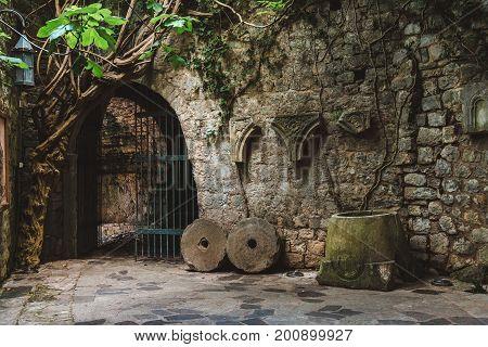 Ancient stone ruins with ivy, fortress wall and gates in Old Bar town, Montenegro. Stari Bar - ruined medieval city on Adriatic coast, Unesco World Heritage Site.