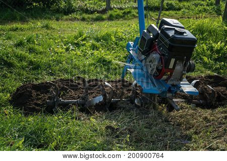 Dumping Of Land In The Garden With A Cultivator