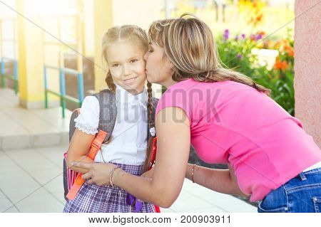 Mother Giving Kiss Goodbye To Children Over School