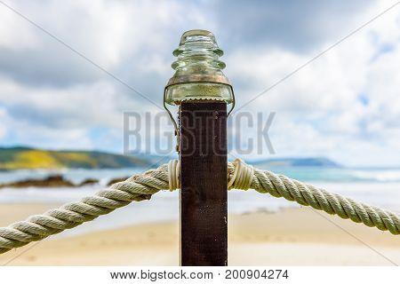 Rope Fence On Wooden Pillar With Glass Lamp On Beach.