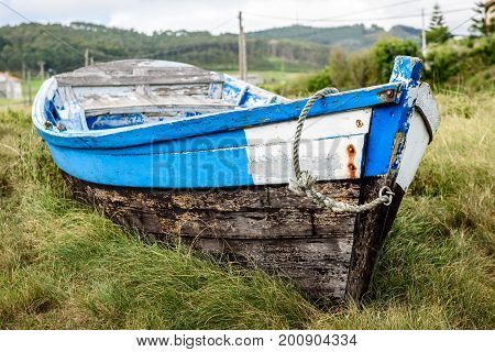 Old Abandoned Wooden Fishing Boat Stranded On Land And Grass.