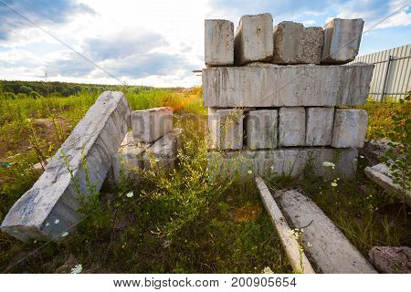 Summer day. On the field near the fence is a construction site. In the frame a group of concrete rectangular blocks stacked in a stack. A blue sky with clouds. Horizontal frame