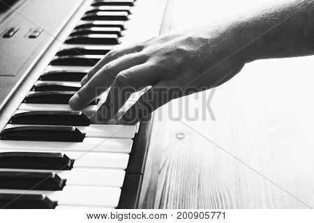 Hand on the keys of a synthesizer. Pianist. Selective focus. Black and white photo.
