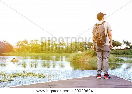 Male Travel Wanderlust Wearing A Cap Standing At The Edge Of Lake Looking Away - Casual Trekking Con
