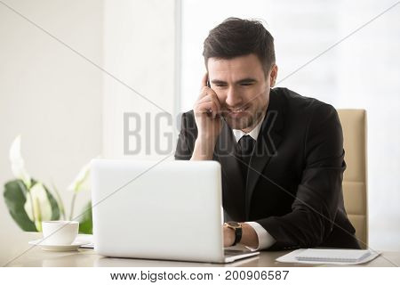 Smiling businessman talking on cellphone sitting at office desk in front of laptop, having successful mobile negotiations with client, manager consulting customer by phone, easy internet banking