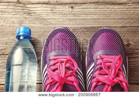 water bottle and light purple pair of running shoes sneakers on dark wooden background. flat top angle view
