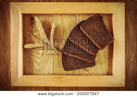 Sliced rye bread and spikelets of rye in a wooden frame on a wooden surface
