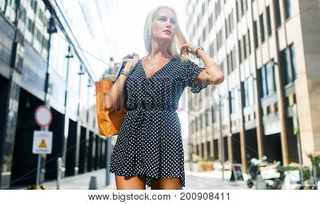 Photo of girl in dress with purchases on city street near buildings