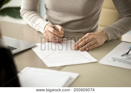 Woman signing document, focus on female hand holding pen, putting signature at official paper, subscribing name in statement with legal value, contract management, good business deal, close up view
