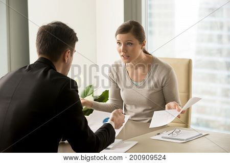 Angry businesswoman arguing with businessman about paperwork failure at workplace, executives having conflict over responsibility for bad work results, partners disputing about contract during meeting