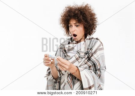 Shocked sick woman wrapped in a blanket looking at thermometer isolated over white background