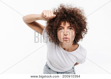 Young casual woman with curly hair knocking on the camera isolated over white background