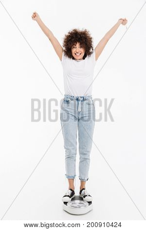 Happy cheerful woman standing on scales and holding her hands up in the air isolated over white background