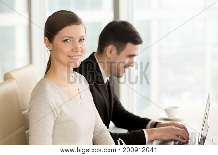 Beautiful smiling businesswoman built successful career posing at workplace with laptop near colleague, ambitious lady looking at camera in office, powerful women in business leadership, portrait