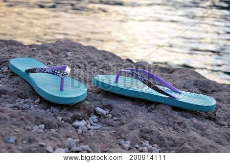 two blue flipflops on the beach close up
