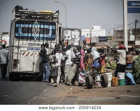 Dakar, Senegal - May 28, 2011 - A group of men and women wait to take public transport