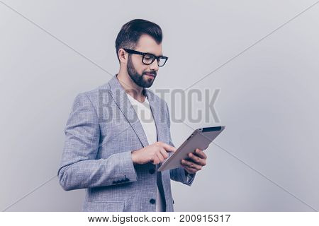 Focused Handsome Young Brunet Bearded Stock-market Broker Is Typing On His Tablet, Standing In A For