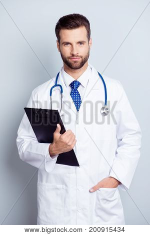 Young Serious Bearded Intern In Uniform And A Tie Is Standing On The White Background, He Is Holding