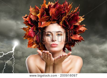 Autumn Woman Blowing Kiss on Cloudy Sky. Beautiful Fashion Model with Fall Leaves Fantasy Autumn Season Concept