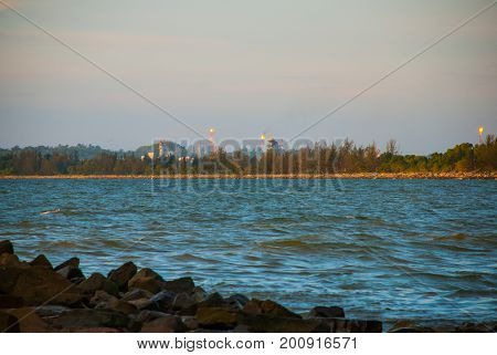 Landscape View Of The Water In The Evening Pipe With The Fire On The Horizon, City Bintulu, Borneo,