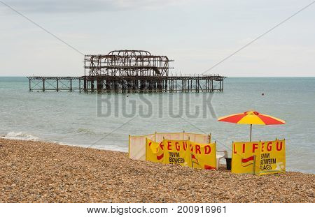 Lifeguard post on the shingle beach at Brighton in East Sussex England. With ruined West Pier in background.