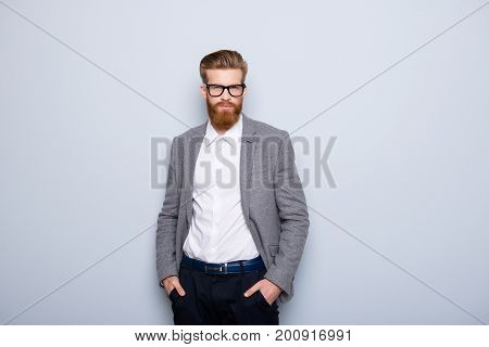 Young Handsome Man In Formalwear With Red Beard And Glasses Holding Hands In Pockets