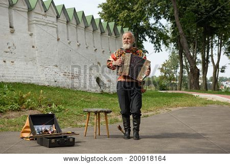 SUZDAL/ RUSSIA - AUGUST 19, 2017. An elderly man in the Russian national costume playing the Russian accordion in front of the Suzdal Kremlin. Suzdal, Russia.
