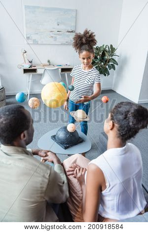 Little girl telling her parents about a big solar system model placed on the coffee table