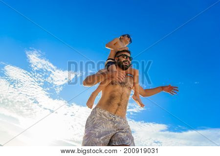Eight Years Old Boy Sitting On Dad's Shoulders. Both In Swimming Shorts And Sunglasses, Having Fun O