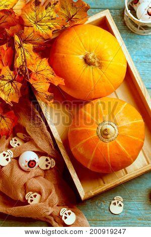 Halloween pumpkins, brown cloth, wooden skulls, maple leaves, eyeballs on blue wooden table