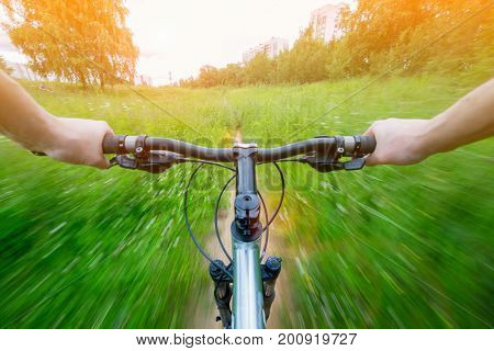 Mountain biking down hill descending fast on bicycle with motion blur. View from bikers eyes and two hand on the handlebars.