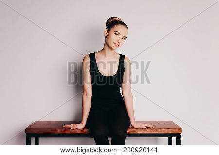 Ballet dancer in black tights on a light background sits on the crossbar. Place for your text.
