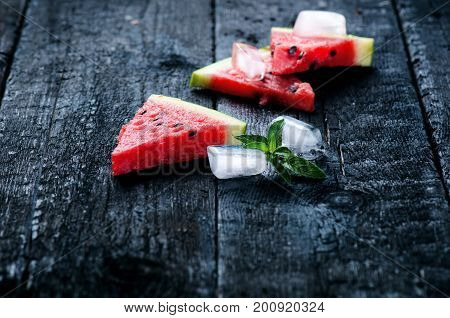Water melon cocktail with slices of fresh melon on a wooden burnt table with ice cubes. Black natural background. Healthy drink. Summer cocktail