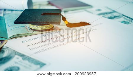 Graduation cap on passport and letter book Businessperson Concept of graduate education MBA abroad in university requires a lot foreign currency Dollars to bring success in famous institution.