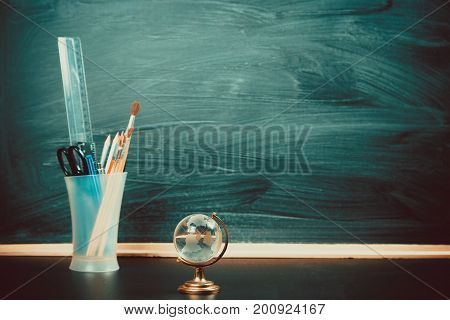 Old Blackboard With Chalk, Books, A Globe And A Pencil. A Beautiful Backdrop For Education, A Free S