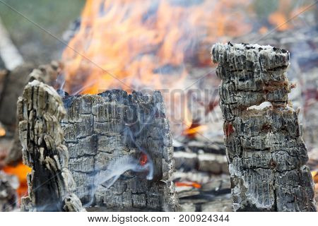 Firewood with red-hot smoldering charcoal embers in purple and bluish hues, top view