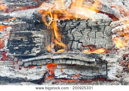 Firewood with red-hot smoldering charcoal embers in purple and bluish hues, top view macro